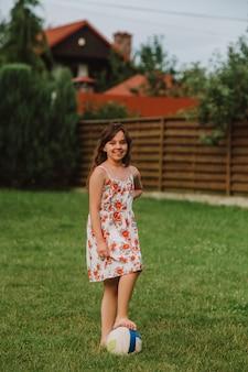 Meisje speelt met de bal in de tuin. zomervakantie.