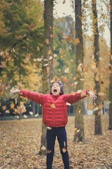 Meisje speelt met de gevallen herfstbladeren tijdens een wandeling in het bos