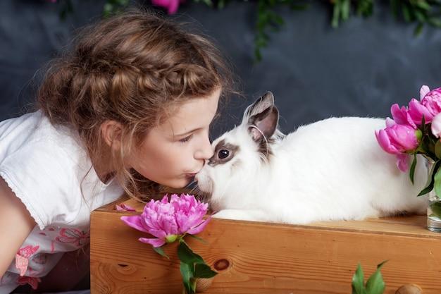 Meisje speelt met echt konijn. kind en wit konijntje op pasen. kid kus huisdier. plezier en vriendschap voor dieren en kinderen.