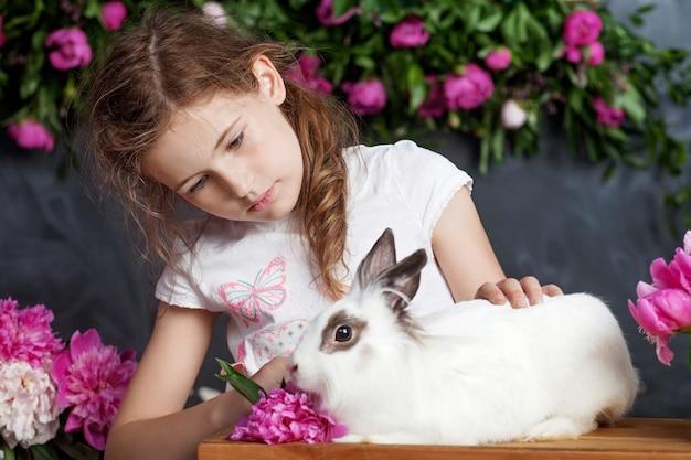 Meisje speelt met echt konijn. kind en wit konijntje op pasen. kinderen en huisdieren spelen. plezier en vriendschap voor dieren en kinderen.