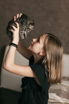 Meisje speelt met een brits klein katje