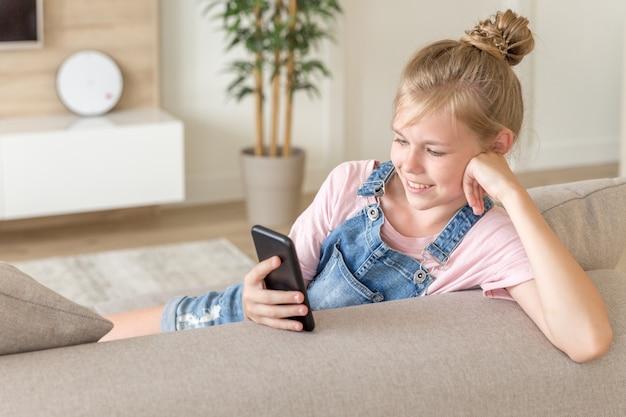 Meisje speelt met een mobiele telefoon thuis op een bank
