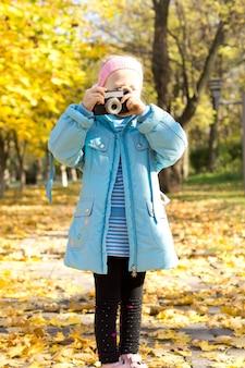 Meisje speelt met een vintage camera fotograferen in een kleurrijke herfst park