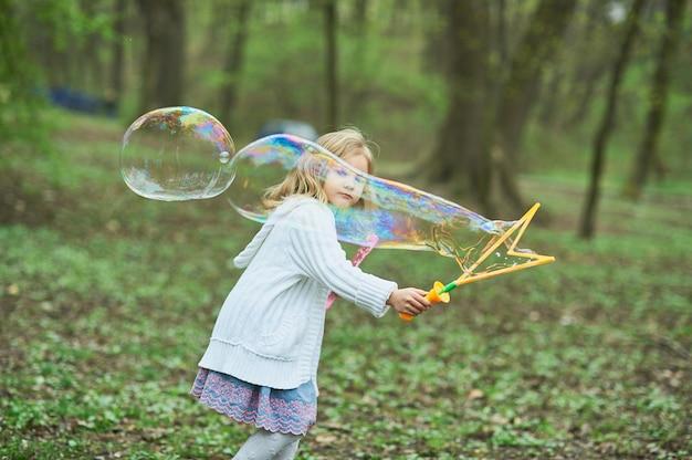 Meisje speelt met gigantische zeepbel, meisje blaast grote bubbels