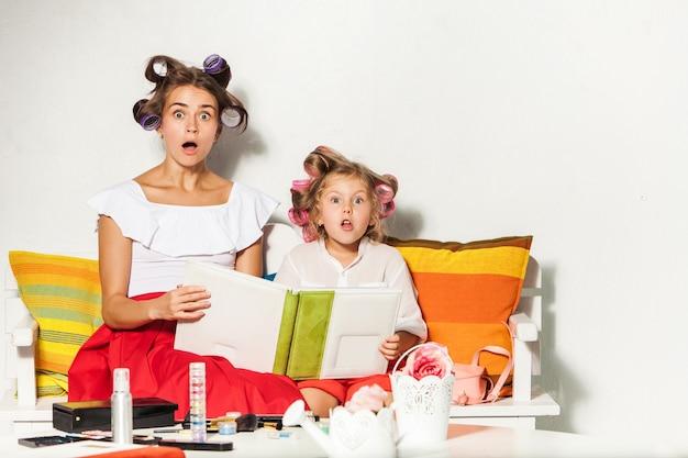 Meisje speelt met haar moeder en kijkt naar een fotoalbum op wit
