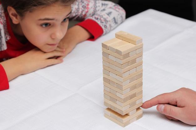 Meisje speelt met haar vader het bouwen van een toren van houten blokken