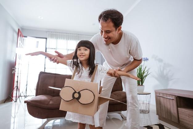 Meisje speelt met kartonnen speelgoedvliegtuig thuis met vader