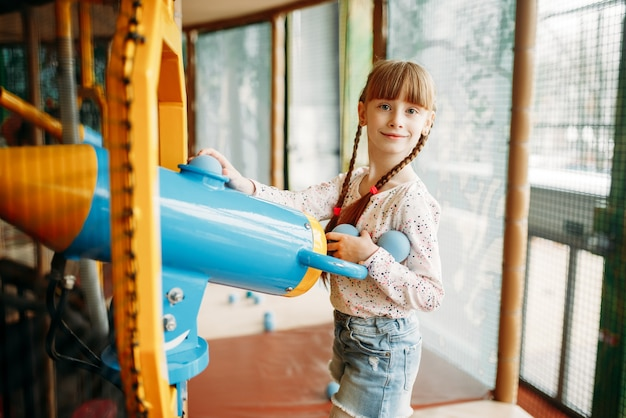 Meisje speelt met luchtpistool in het spelcentrum voor kinderen