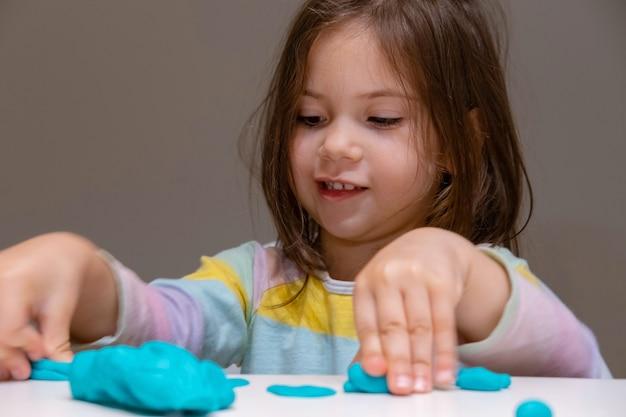 Meisje speelt met plastiline (deeg spelen) op een grijze achtergrond.