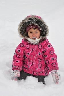 Meisje speelt met sneeuw in de winter. kind eet sneeuw