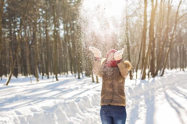 Meisje speelt met sneeuw in het park. gelukkige jonge vrouw die plezier heeft in de sneeuw