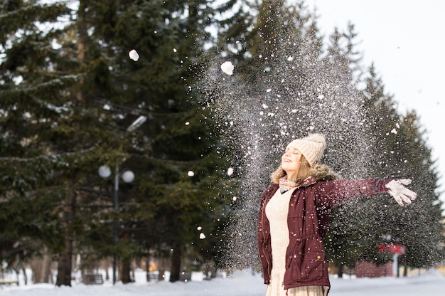 Meisje speelt met sneeuw in park. portret van het gelukkige meisje dat besneeuwde winterkleren draagt