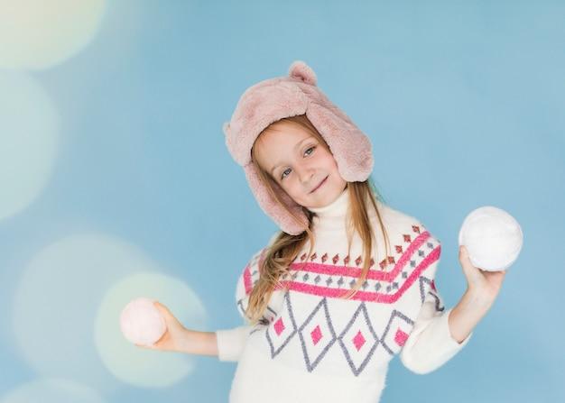 Meisje speelt met sneeuwballen