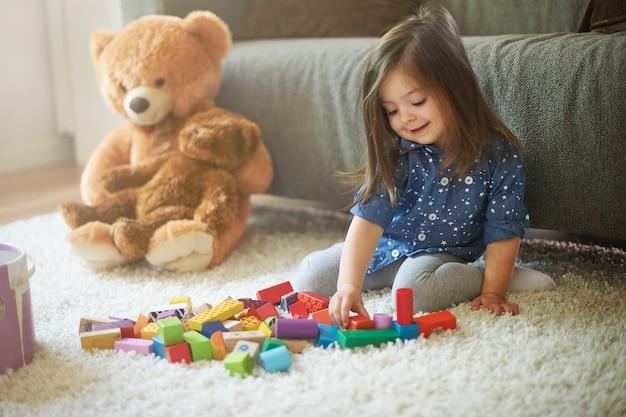 Meisje speelt met speelgoed in de woonkamer