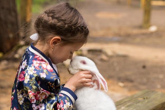 Meisje speelt met wit konijn buiten