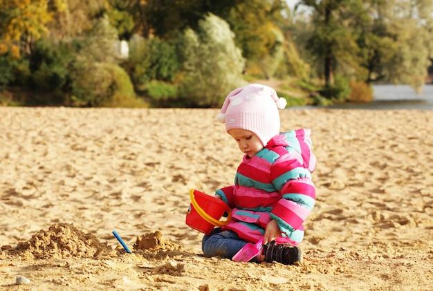 Meisje speelt met zand op het strand van de herfst