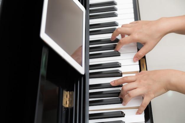 Meisje speelt piano tijdens het lezen van bladmuziek van haar tablet
