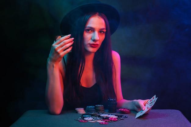 Meisje speelt poker aan een tafel met kaarten en chips in een casino. gokconcept
