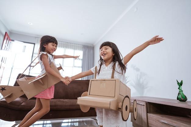 Meisje speelt thuis met kartonnen speelgoedvliegtuig