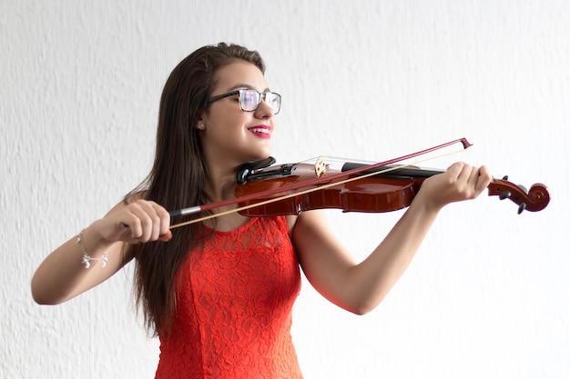 Meisje speelt viool met witte achtergrond.