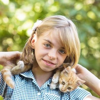 Meisje spelen met kitten buiten in het park