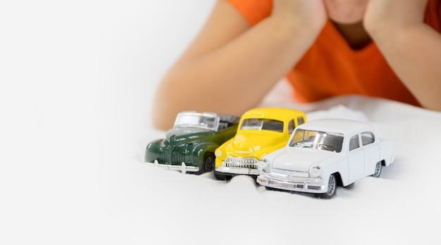 Meisje spelen met witte speelgoedauto. zittend op het witte laken. glimlachend. voorschoolse kinderen.