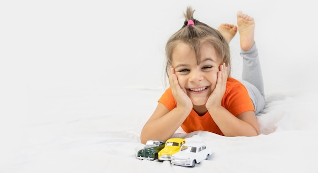 Meisje spelen met witte speelgoedauto. zittend op het witte laken. glimlachend.
