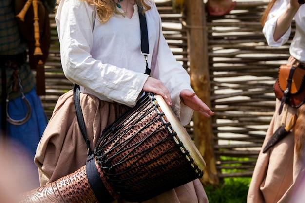 Meisje spelen op djembe-trommel op straat