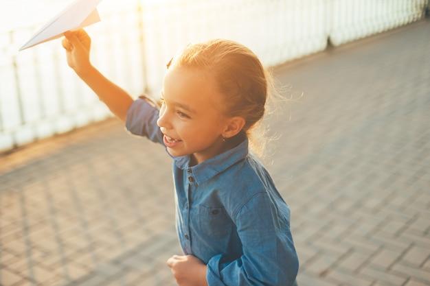 Meisje spelen, uitgevoerd met speelgoed papieren vliegtuigje