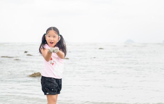 Meisje spelen zand op het strand