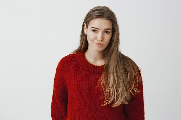 Meisje spreekt minachting uit voor rivaal. portret van ontevreden niet onder de indruk mooie vrouw in modieuze rode losse trui, grijnzend van minachting, twijfelen of ze persoon kon vertrouwen