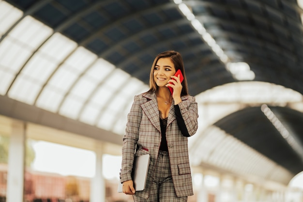 Meisje spreekt op een mobiele telefoon, glimlacht en bedrijf laptop