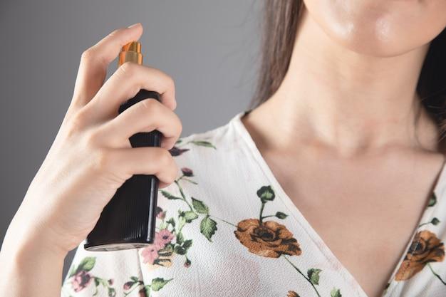 Meisje sprenkelt parfum over zichzelf
