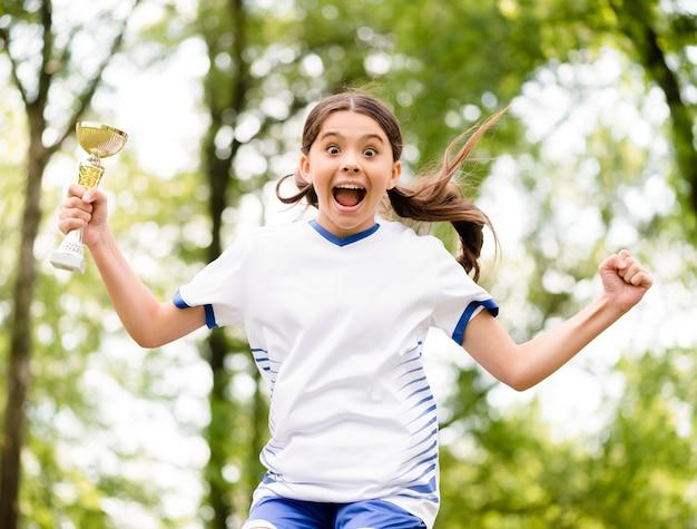 Meisje springt na het winnen van een voetbalwedstrijd
