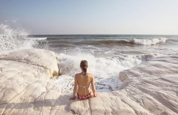 Meisje springt op zeegolf