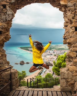 Meisje springt van opwinding op een deuropening met de zee