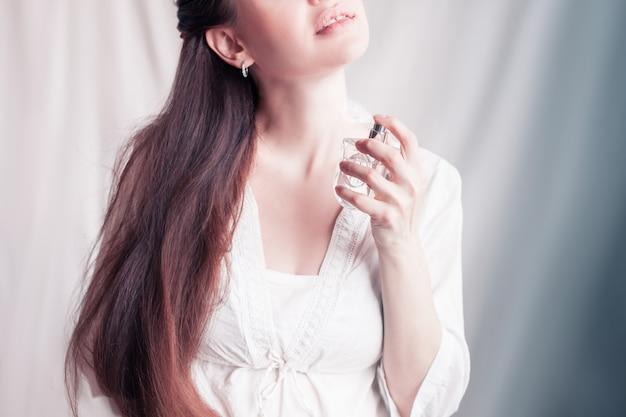 Meisje spuit zichzelf parfum op haar nek