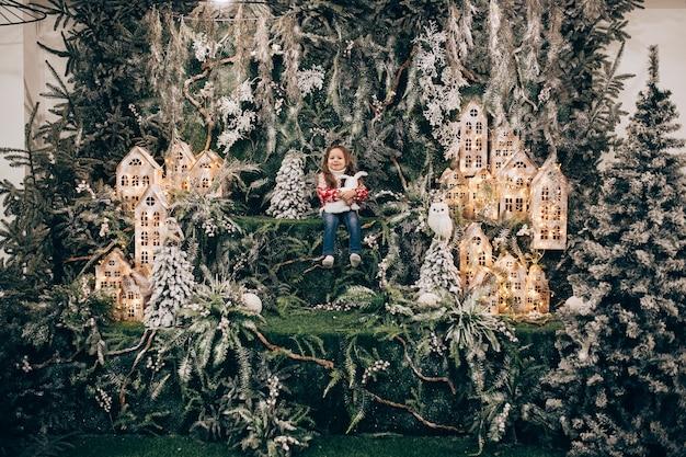 Meisje staande op het bovenste niveau van kerstversiering