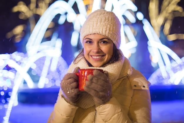 Meisje staande over winter kerst stad achtergrond sneeuw sneeuw drifts staat warme jas hoed houdt
