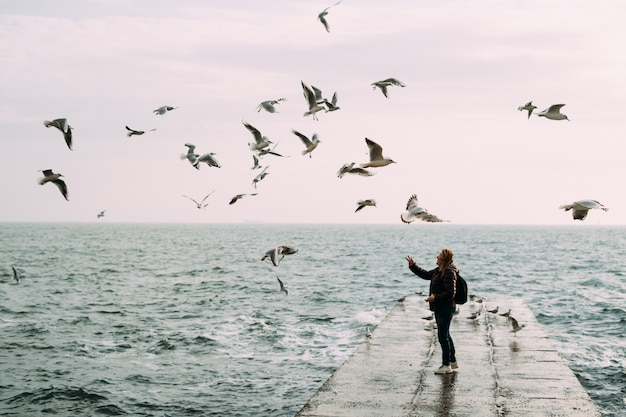 Meisje staat bij de zee op een pier met een rugzak en voedt de meeuwen.