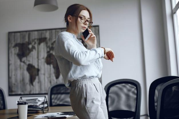Meisje staat bij het raam. vrouw praten aan de telefoon. brunette kijkt naar haar horloge
