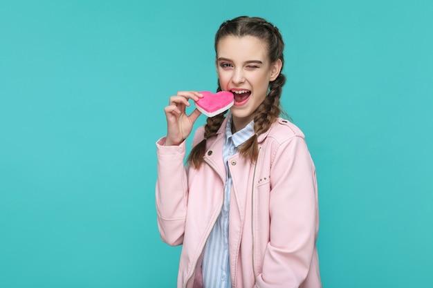Meisje staat en houdt roze hartvorm vast en kijkt naar de camera en probeert te bijten