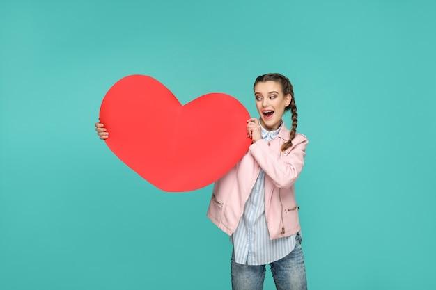Meisje staat en houdt vast en kijkt naar grote rode hartvorm met verrast gezicht