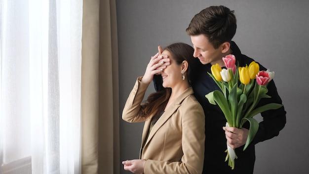 Meisje staat en kijkt thuis uit het raam. achter de vriend komt, sluit zijn ogen en geeft een boeket tulpen