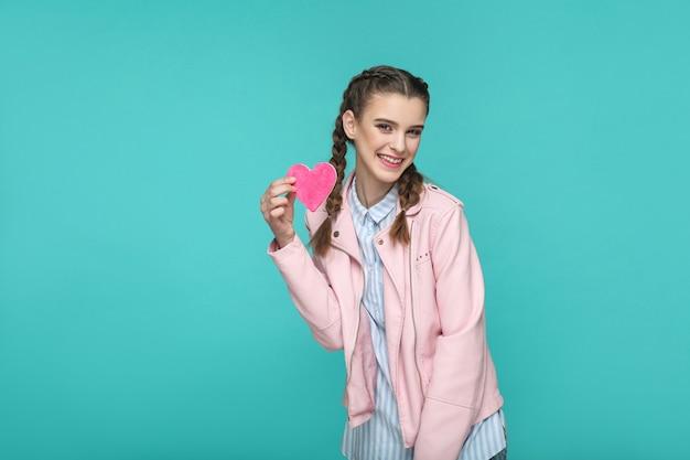 Meisje staat en toont een roze hartvorm en kijkt naar de camera met een brede glimlach