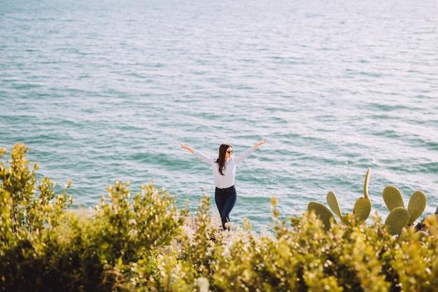 Meisje staat met de handen omhoog in de buurt van zee