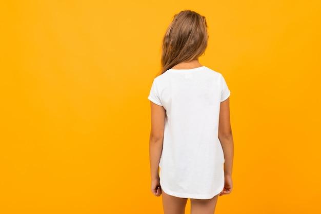 Meisje staat met haar rug in een wit t-shirt op een oranje muur