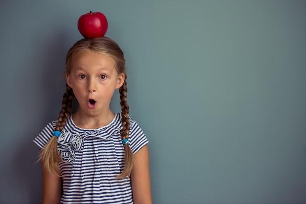 Meisje staat met rode appel op haar hoofd