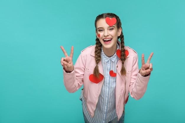 Meisje staat met te veel geplakte rode haert-stickers die naar de camera kijken en de overwinning van het vredesteken