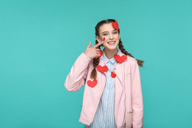 Meisje staat met te veel geplakte rode hartstickers die naar de camera kijken met een brede glimlach